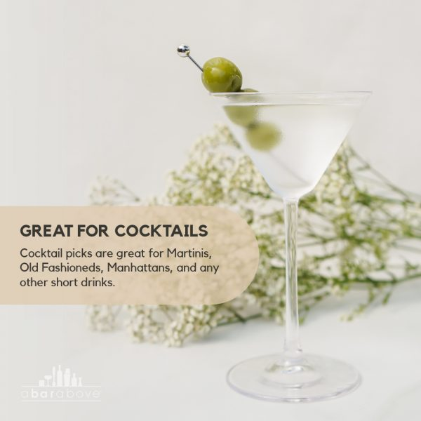 short stainless steel cocktail pick in martini with olives