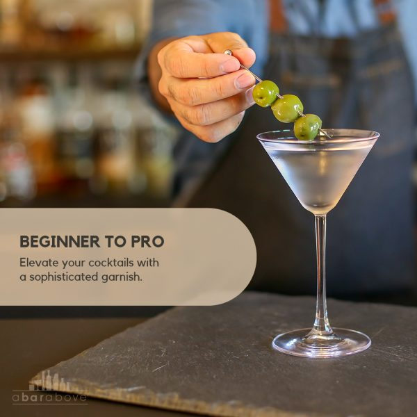 short stainless steel cocktail pick with pierced olives in martini